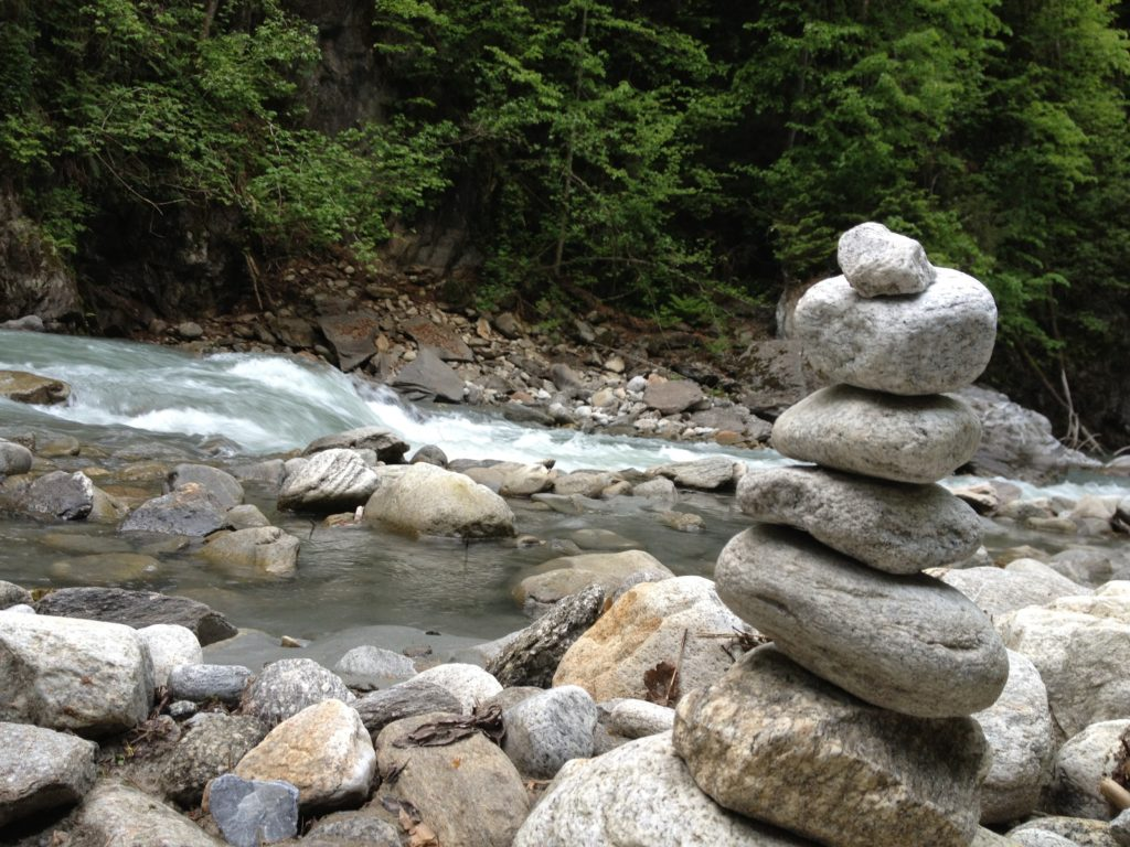 Joy of resilience Tower of rocks next to a creek symbolizing the resilience journey